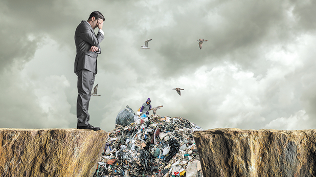 A distraught businessman standing at the edge of a cliff with his head in his hands.